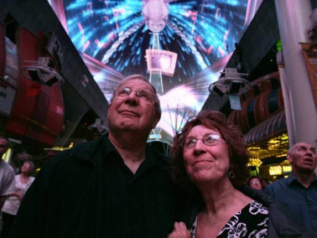 "Lee and Shirley Bauer of Rapid City, S.D., watch as ""The Doors: Strange Days in Vegas"" plays on the huge screen at the Fremont Street Experience in downtown Las Vegas. Complex math formulas were used to make this canopy show more high-tech than previous shows."