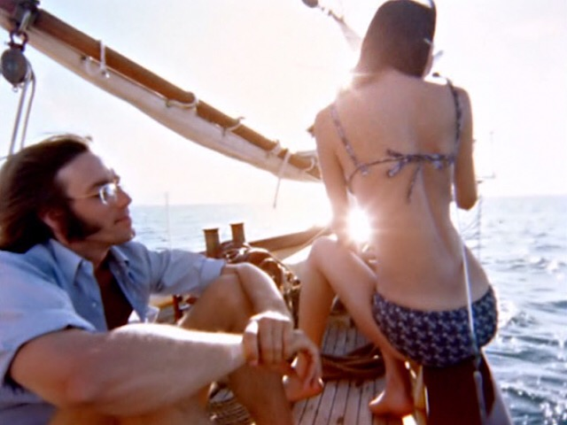 Still image from Feast of Friends. Ray Manzarek with bikini-clad mystery girl.
